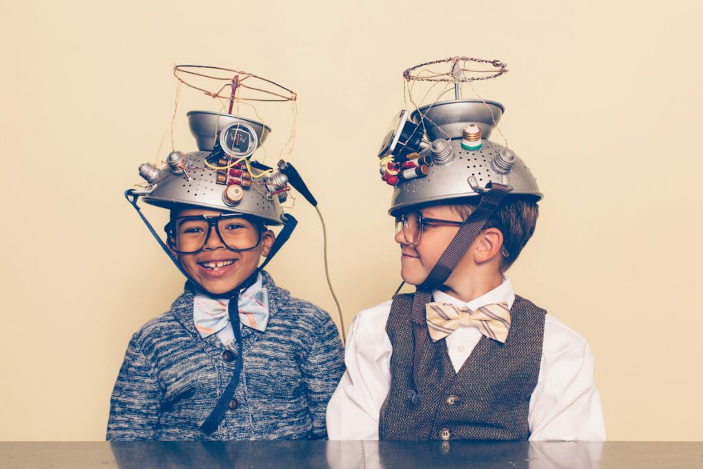 Two nerd boys dressed in casual clothing, glasses and bow ties experiment with a homemade science project. They are both smiling and sitting at a table, and one is looking at the other with helmets on their heads in front of a beige background. Retro styling.