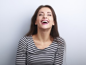Happy natural laughing young casual woman with wide open mouth and closed eyes on blue background