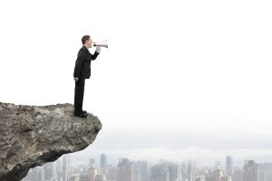 Businessman using megaphone yelling on cliff with city skyline background
