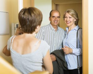 Smiling mature family couple visiting daughter at home