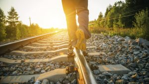 Man legs walking on railway.